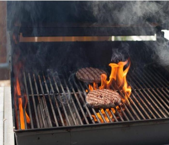 Fire beginning on a grill from hamburger grease